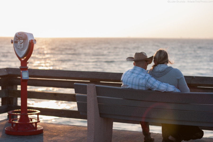 Couple on a bench at a pier, looking at the sunset