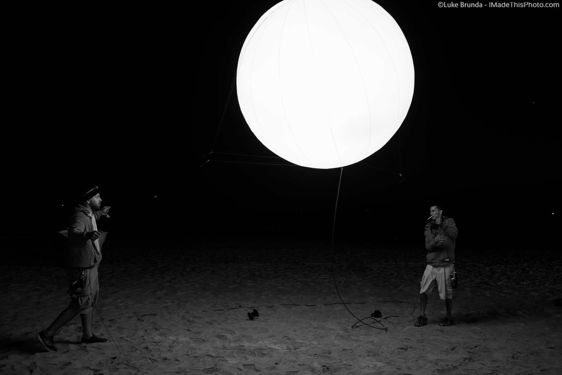 Two men raising a lighted orb in the dark.